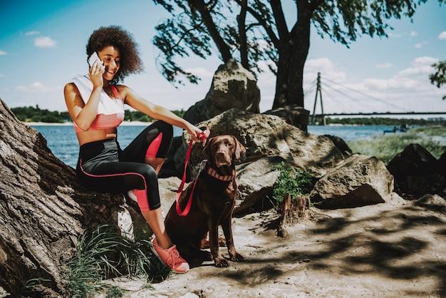 Donna africana con cane parlando al telefono. Foto Premium
