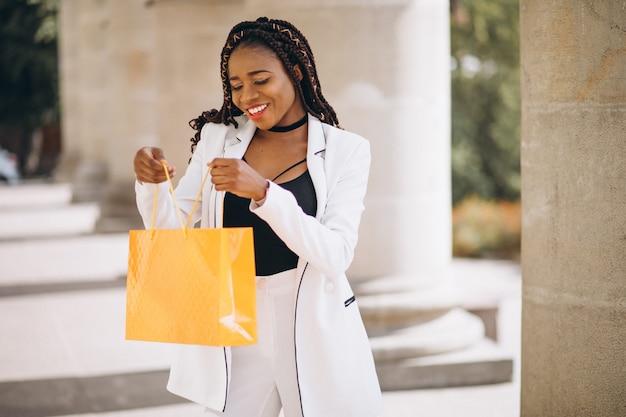 Donna africana con i sacchetti della spesa gialli Foto Gratuite