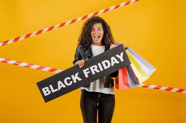 Donna africana sorridente con il segno di venerdì nero e sacchetti della spesa variopinti isolati sopra giallo con nastro adesivo Foto Premium