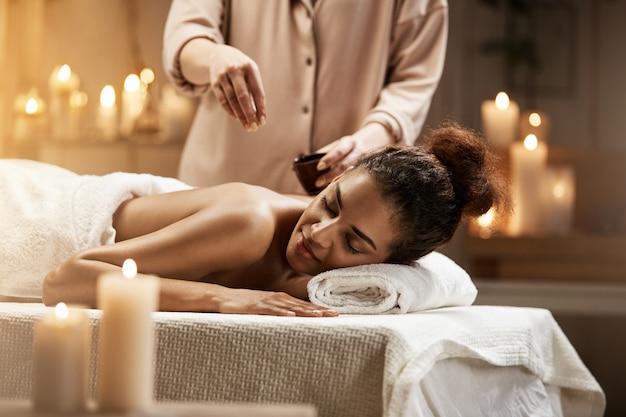 Donna africana tenera che si rilassa godendo del massaggio sano della stazione termale con olio. Foto Gratuite