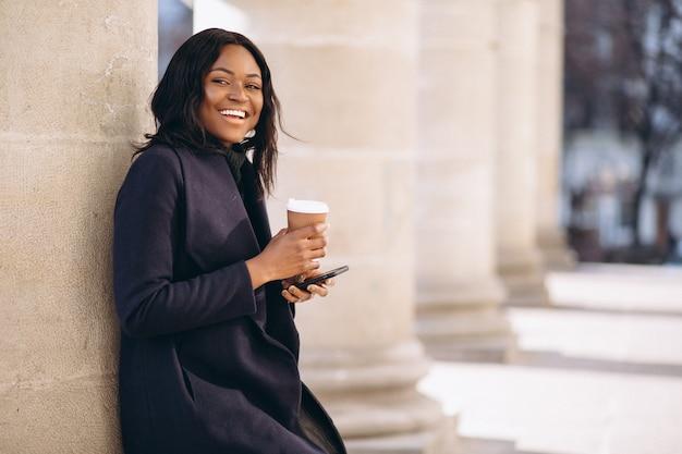 Donna afroamericana con il telefono che beve caffè Foto Gratuite