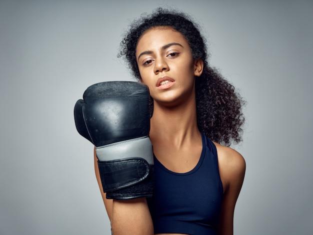 Donna afroamericana dalla pelle scura che posa in una tuta sportiva e che fa sport Foto Premium