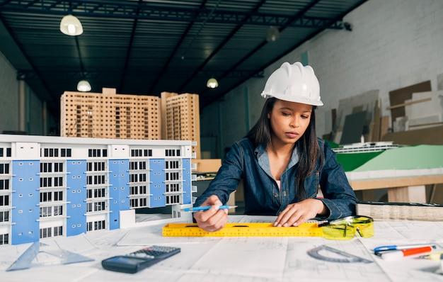 Donna afroamericana nel casco di sicurezza che lavora vicino al modello di costruzione Foto Gratuite