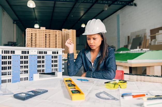 Donna afroamericana pensierosa nel casco di sicurezza vicino al modello di costruzione Foto Gratuite