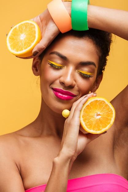 Donna afroamericana sensuale verticale con gli occhi chiusi che tengono due parti dell'arancia e che godono degli agrumi isolati, sopra la parete gialla Foto Gratuite