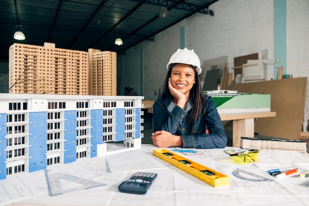 Donna afroamericana sorridente nel casco di sicurezza vicino al modello di costruzione Foto Gratuite