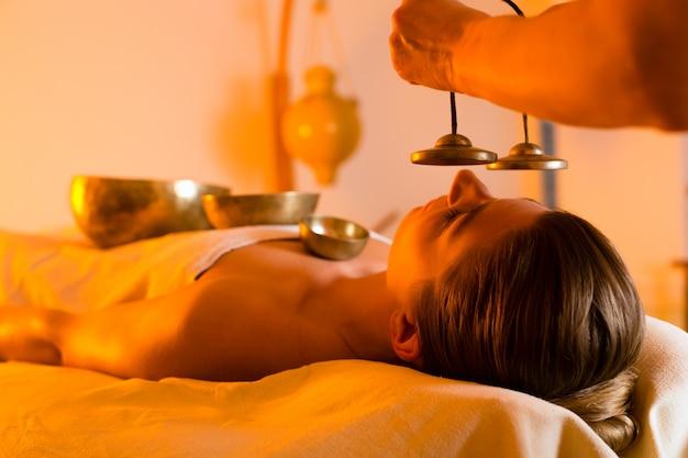 Donna al massaggio benessere con campane tibetane Foto Premium