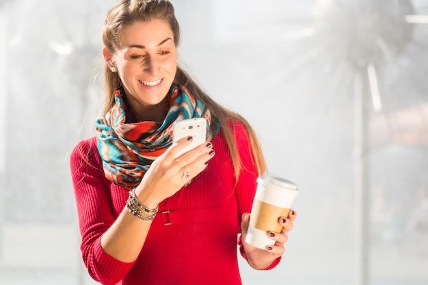 Donna alla fontana con telefono e caffè Foto Premium