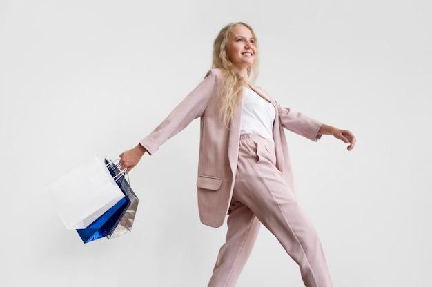Donna alla moda che cammina con i sacchetti della spesa Foto Gratuite