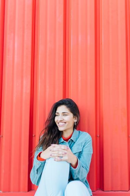 Donna alla moda che distoglie lo sguardo seduta su sfondo luminoso Foto Gratuite