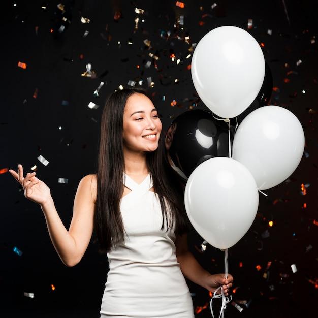Donna alla moda che posa con gli aerostati alla festa Foto Gratuite
