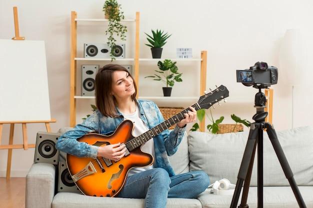 Donna alla moda che si ricodifica mentre suona la chitarra Foto Gratuite