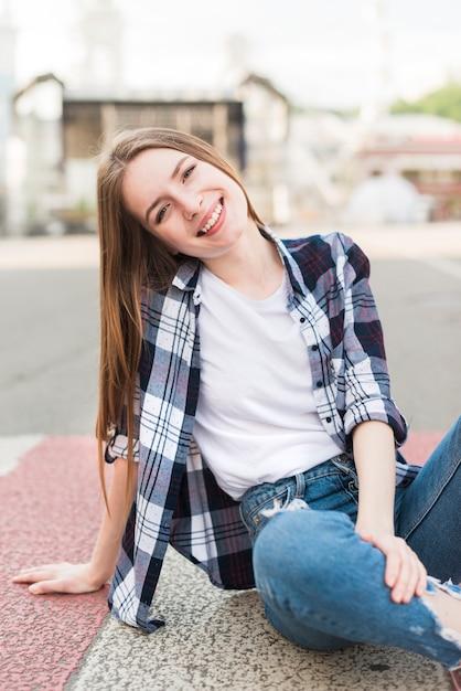 Donna alla moda che si siede sulla strada che guarda l'obbiettivo Foto Gratuite