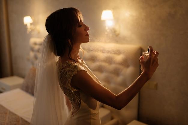 Donna alla moda del profumo dello spruzzo della sposa che indossa un profumo tenero dello spruzzo del vestito bianco. elegante bottiglia di vetro di profumo nelle mani. ragazza con il trucco e una bottiglia di profumo. preparazione del matrimonio. Foto Premium
