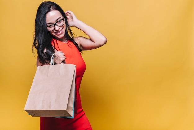 Donna alla moda in abito con borse della spesa Foto Gratuite
