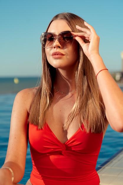 Donna alla moda in bikini rosso che si siede vicino allo stagno Foto Premium
