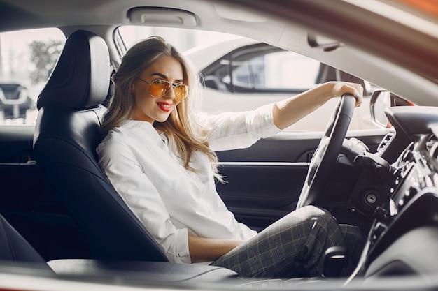 Donna alla moda in un salone di auto Foto Gratuite