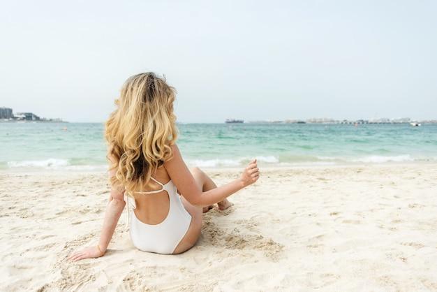 Donna alla spiaggia del dubai che porta i costumi da bagno bianchi Foto Premium