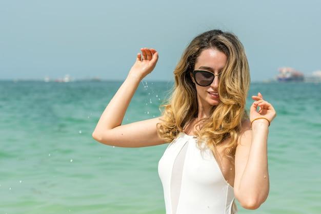 Donna alla spiaggia del dubai in costumi da bagno bianchi Foto Premium