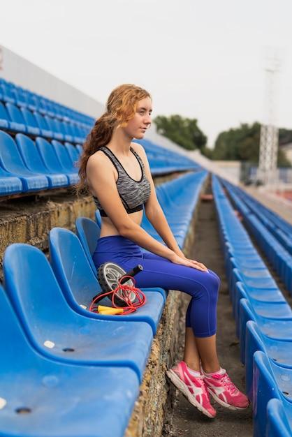 Donna allegra alla seduta dello stadio Foto Gratuite