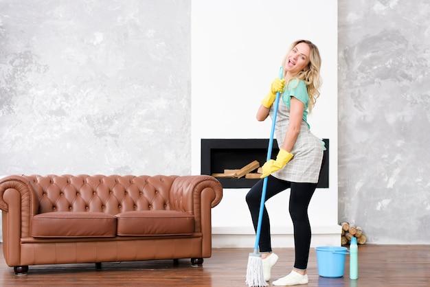 Donna allegra che balla con la scopa vicino al secchio e alla bottiglia del detersivo Foto Gratuite