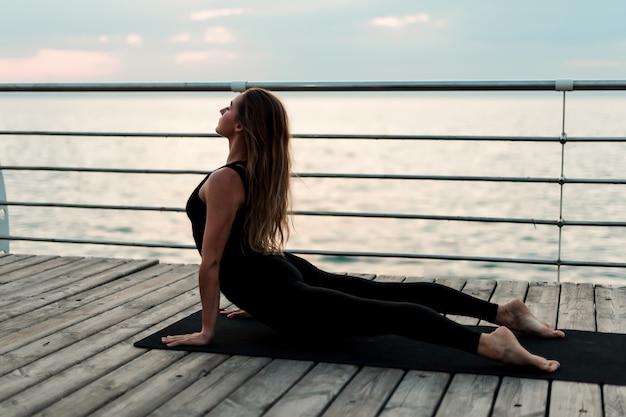 Donna allegra che fa asana di yoga sul mare di mattina Foto Premium