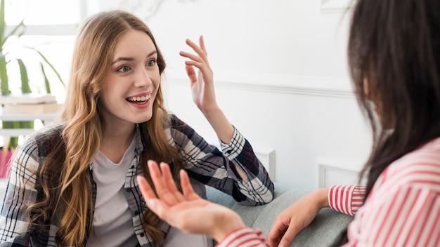 Donna allegra che gesturing parlando all'amico Foto Gratuite