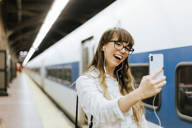 Donna allegra che ha una video chiamata ad una piattaforma del sottopassaggio Foto Gratuite