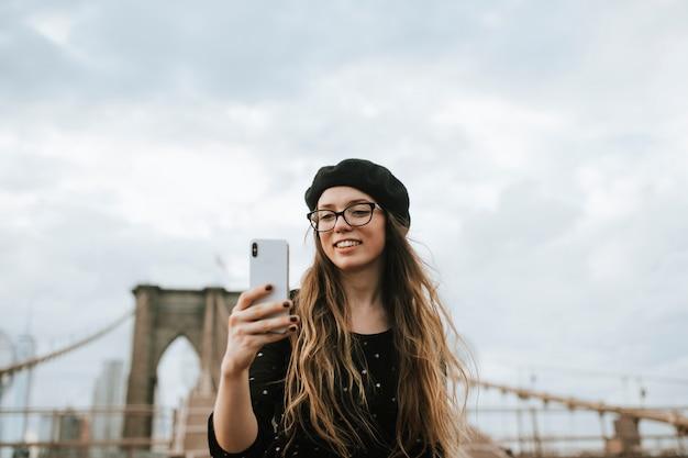 Donna allegra che prende un selfie con il ponte di brooklyn, usa Foto Premium