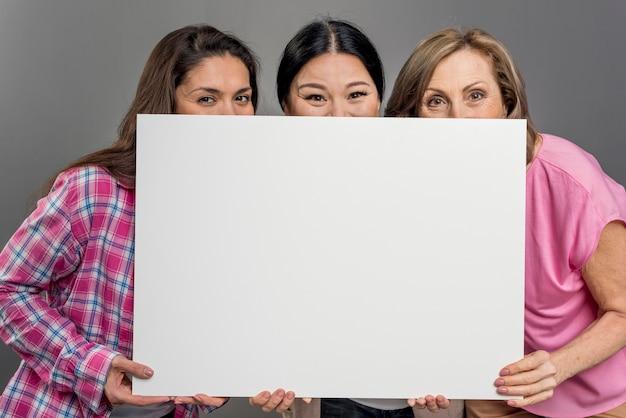 Donna allegra che si nasconde sotto il foglio di carta bianco Foto Gratuite