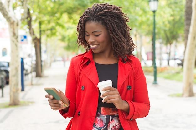 Donna allegra che utilizza smartphone nel parco Foto Gratuite