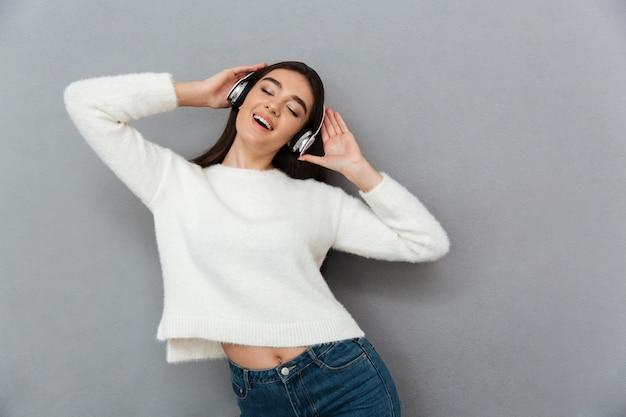 Donna allegra del brunette nella musica d'ascolto delle cuffie e del maglione Foto Gratuite