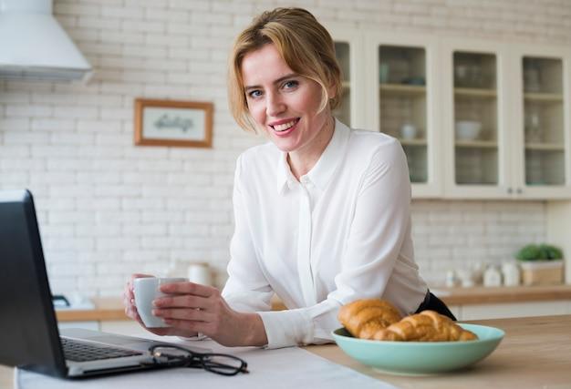 Donna allegra di affari con caffè facendo uso del computer portatile Foto Gratuite