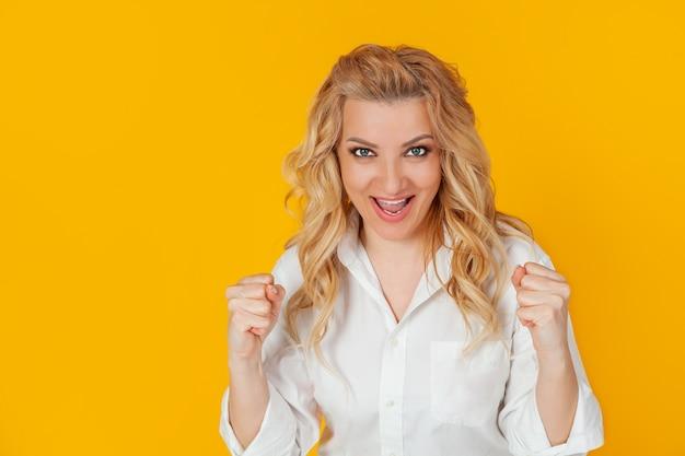 Donna allegra e felice che solleva le sue mani con il suo pugno Foto Premium