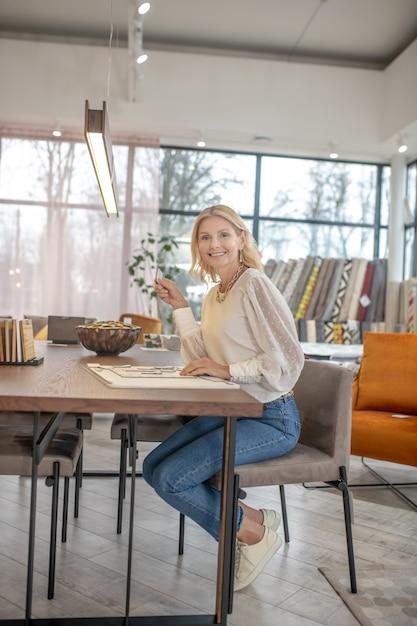 Donna allegra in jeans, seduto a un tavolo in una grande stanza luminosa di un negozio di mobili, sorridente. Foto Premium