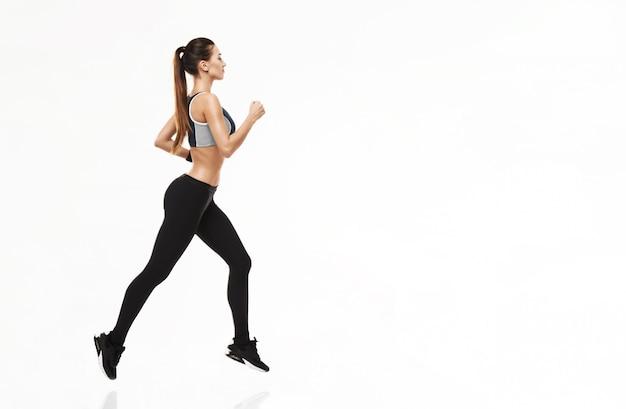 Donna allegra nell'addestramento degli abiti sportivi che funziona sul bianco. Foto Gratuite