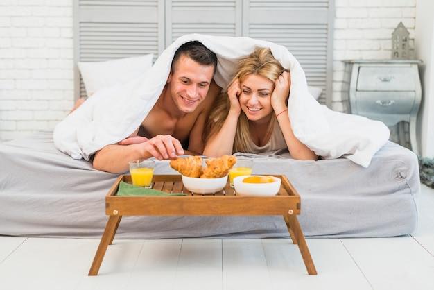 Tavoli Per Colazione A Letto : Donna allegra vicino al giovane a letto sotto coperta vicino al