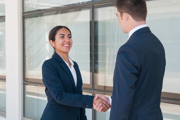 Donna ambiziosa sorridente di affari che dice arrivederci al socio Foto Gratuite