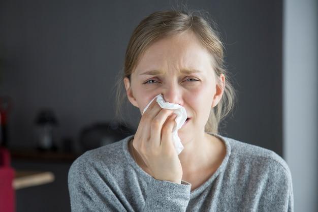 Donna ammalata infelice che soffia il naso con il tovagliolo, che guarda l'obbiettivo Foto Gratuite