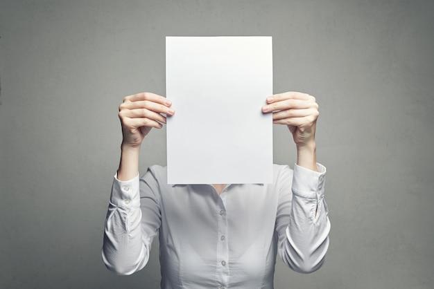 Donna anonima che copre il viso con un foglio di carta Foto Premium