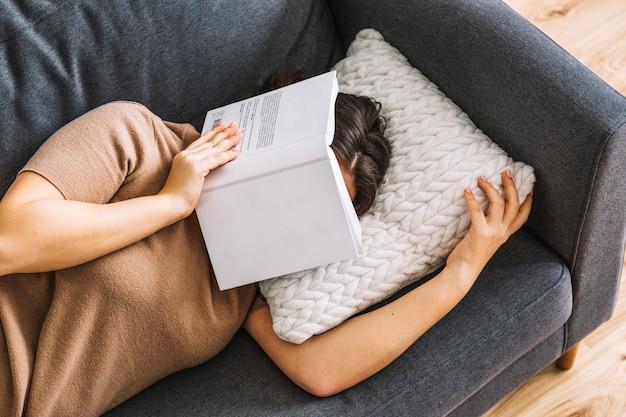 Donna anonima con il libro che dorme sul divano Foto Gratuite