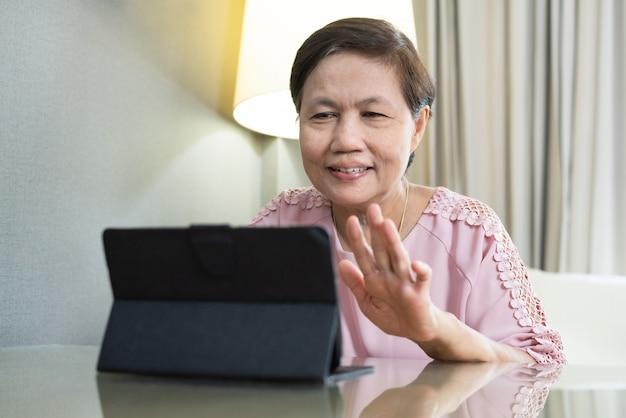 Donna anziana asiatica sorridente che fa video chiamata sulla compressa digitale durante la quarantena e isolata a casa. Foto Premium