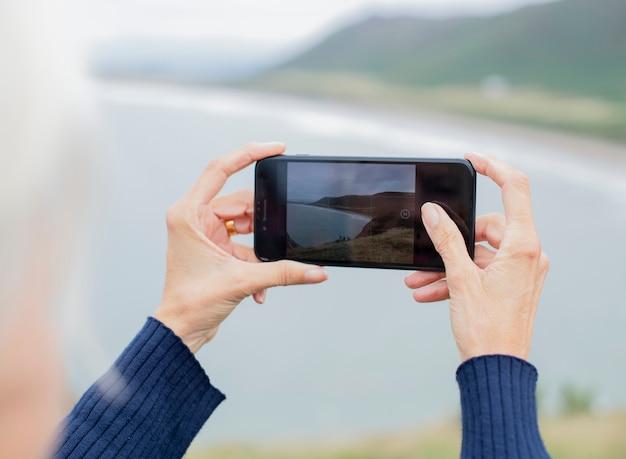 Donna anziana che cattura una foto dell'oceano Foto Gratuite