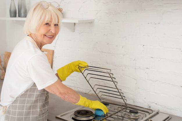Donna anziana che lava la stufa con i guanti Foto Gratuite