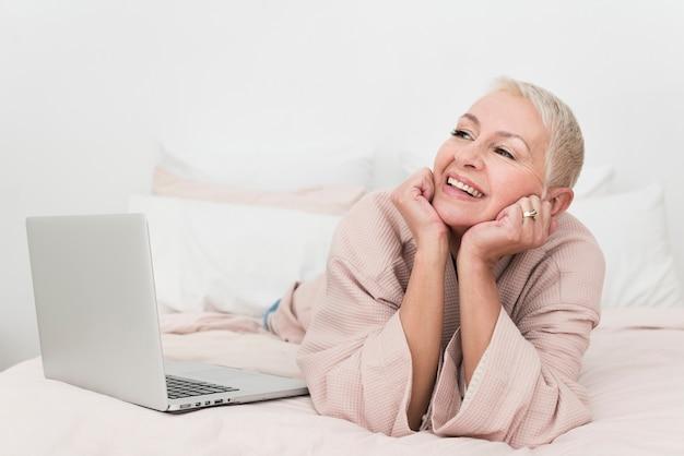 Donna anziana che posa in accappatoio con il computer portatile a letto Foto Gratuite