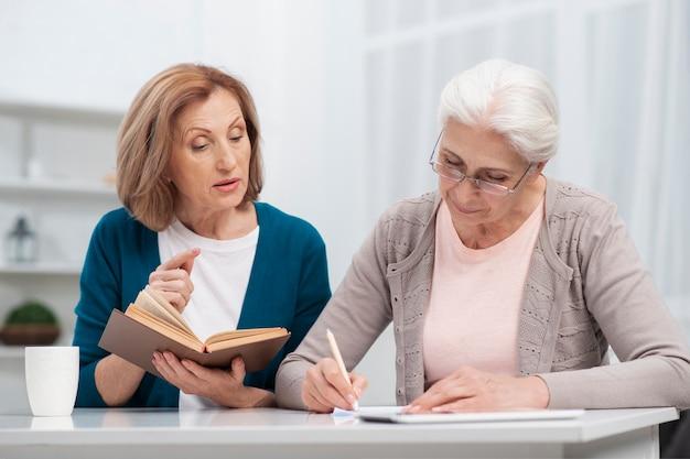Donna anziana che prende insieme le note Foto Gratuite