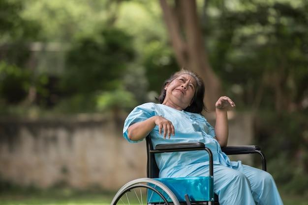 Donna anziana che si siede sulla sedia a rotelle con la