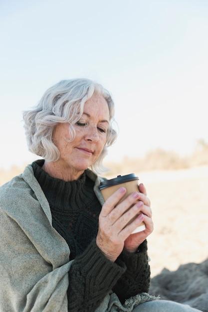 Donna anziana del colpo medio con caffè all'aperto Foto Gratuite