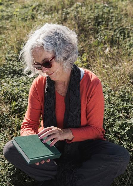 Donna anziana del colpo medio con il libro all'aperto Foto Gratuite