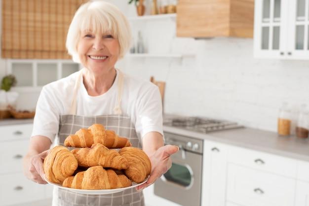Donna anziana di smiley che tiene una zolla con i croissant Foto Gratuite